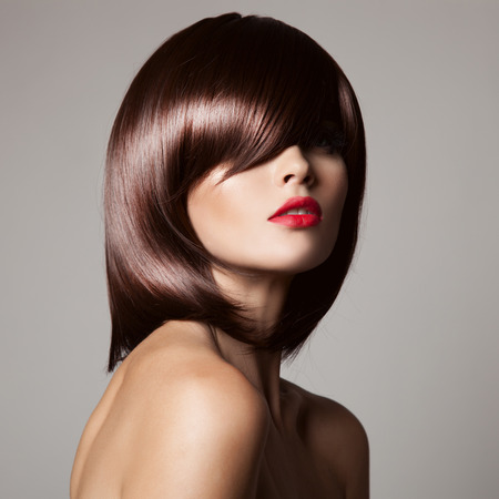 salon hair: Beauty model with perfect long glossy brown hair. Close-up portrait. Stock Photo
