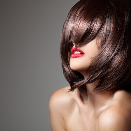 hair cut: Beauty model with perfect long glossy brown hair. Close-up portrait. Stock Photo