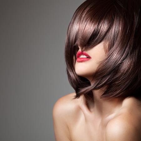 knippen: Schoonheid model met perfecte lange glanzend bruin haar. Close-up portret.