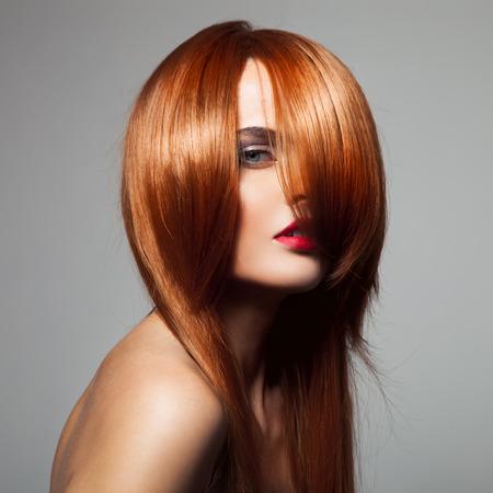 pelo rojo: Modelo de la belleza con el pelo largo de color rojo brillante perfecto. Retrato de primer plano. Foto de archivo