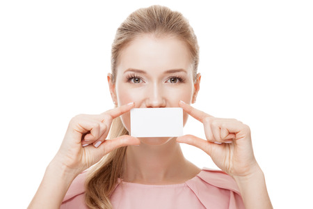 Beautiful woman holding white card at front of her lips with copy space .  Isolated.