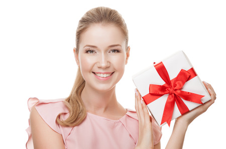 Young happy smiling woman with a gift in hands. Isolated on white background.