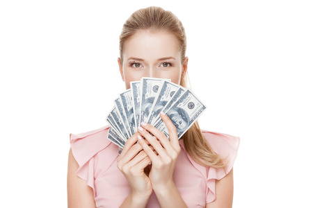 Young happy woman with dollars in hand. Isolated on white background.