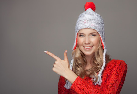 closeup portrait: Beautiful smiling woman wearing winter clothing. Pointing on copyspace. Stock Photo