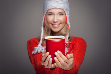 Beautiful blonde woman with an aromatic hot coffee in hands. Focus on red cup. photo