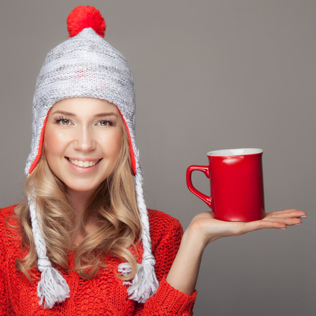 sweater girl: Beautiful blonde woman with an aromatic hot coffee in hand.