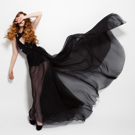 fluttering: Fashion woman in fluttering black dress. White background.