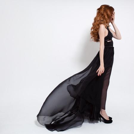 Moda donna in svolazzante abito nero. Sfondo bianco. Archivio Fotografico - 37109423
