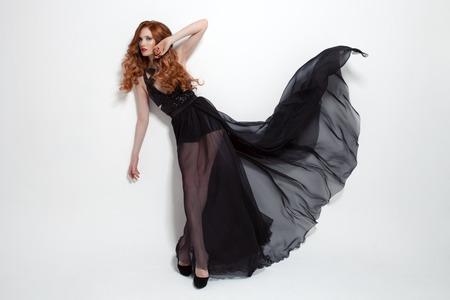 modelos negras: Mujer de moda en el vestido negro que agita. Fondo blanco.