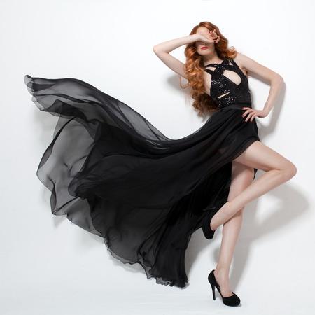 Mujer de moda en el vestido negro que agita. Fondo blanco.