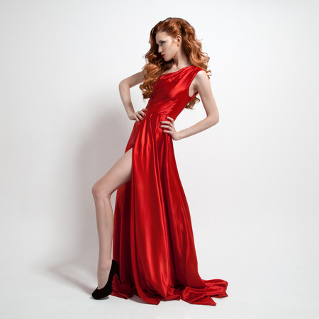 Young beautiful woman in red dress. White background. photo