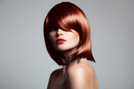 hair cut: Beautiful red hair model with perfect glossy hair. Close-up portrait.