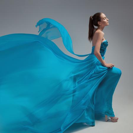 바람이 잘 통하는 파란색 드레스를 펄럭이는 아름다운 여자. 회색 배경입니다. 스톡 콘텐츠