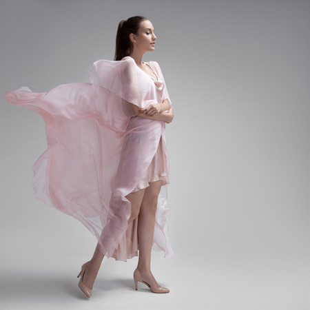 fluttering: Beautiful woman in fluttering airy pink dress. Gray background.