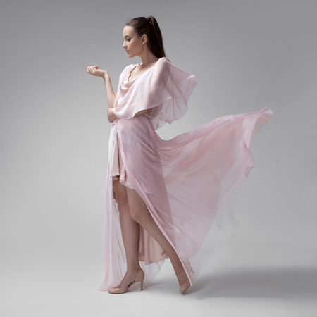 Beautiful woman in fluttering airy pink dress. Gray background. photo
