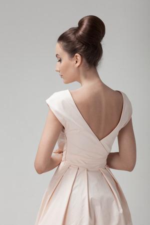 Beautiful woman in pink retro dress. Gray background. photo