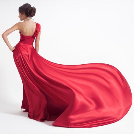 Jeune femme de beauté en robe rouge flottant. Fond blanc.
