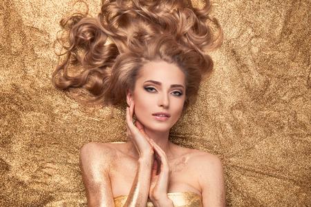 look make: Fashion Beauty Girl Lying On Golden Glitter.