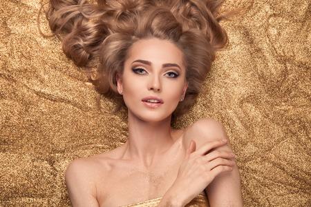glitter gloss: Fashion Beauty Girl Lying On Golden Glitter.