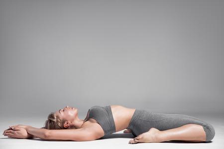 atletismo: Longitud total de un cuerpo de la mujer se extiende joven. Fondo gris.