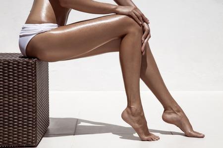 hot girl nude: Beautiful woman tan legs. Against white wall.