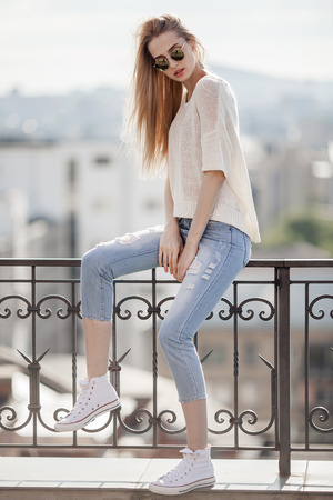 fashion girl: Fashion model. Summer look. Jeans, sweater, sunglasses. Stock Photo