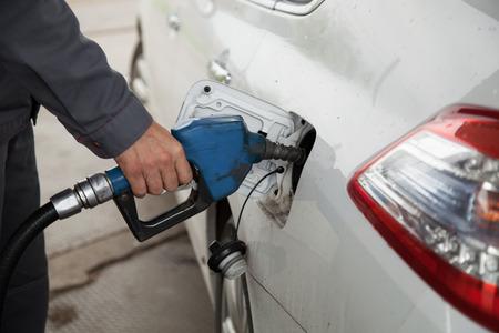 gasolinera: Bombeo Mano masculina de gasolina en el coche, reabastecimiento de combustible con la boquilla en la gasolinera