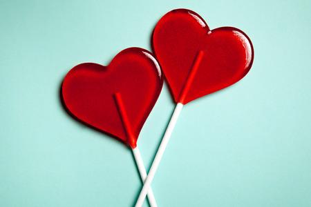 golosinas: Dos piruletas. Corazones rojos. Dulce. Concepto del amor. Día de San Valentín.