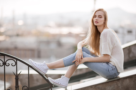 fashion style: Fashion model. Summer look. Jeans, sneakers, sweater.