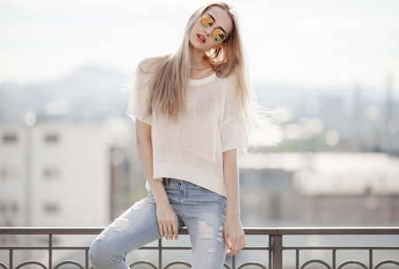 moda: Modella. Estate look. Jeans, maglione, occhiali da sole.