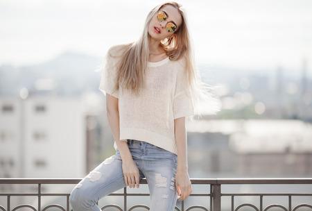 moda ropa: Modelo. Mirada de Verano. Jeans, suéter, gafas de sol.
