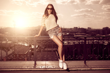 clothing model: Beautiful brunette young woman wearing sunglasses, shorts, white top posing above sunset city background. Hot summer.