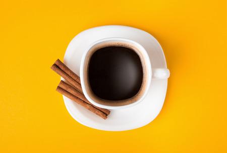 amarillo y negro: taza de café fresco sobre fondo amarillo, ver desde arriba