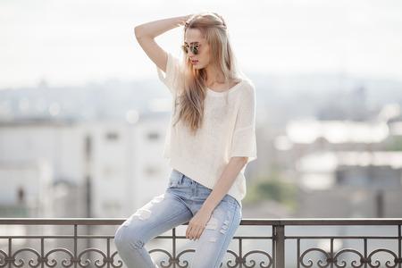 Model. Zomerlook. Jeans, trui, zonnebril.