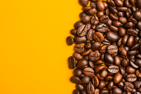 text space: Roasted coffee beans close up. Yellow background. Space for text.