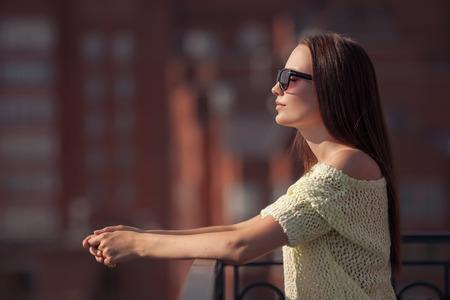 belle brunette: Belle fille dans des lunettes de soleil en appr�ciant la fra�cheur. Coucher de soleil l'�t�.