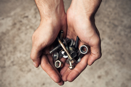 rusty nail: Iron rusty tools bolts and screws in mans hands.