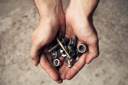 tornillos: Planche herramientas pernos y tornillos oxidados en mans manos.