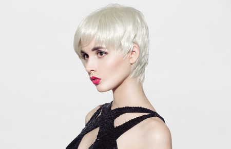 Close-up portret van mooi model met perfect glanzend blond haar en heldere make-up. Witte achtergrond. Ruimte voor tekst.