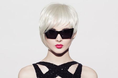 완벽 한 광택 금발 머리와 선글라스 아름다운 모델의 확대하여 세로. 흰 바탕. 텍스트를위한 공간입니다. 스톡 콘텐츠