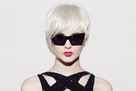 Close-up portrait of beautiful model with perfect glossy blond hair and sunglasses. White background. Space for text.