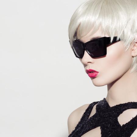 Close-up portret van mooie model met een perfecte glanzend blond haar en een zonnebril. Witte achtergrond. Ruimte voor tekst.