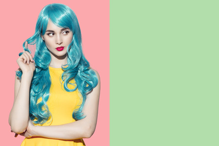 Pop art woman portrait wearing blue curly wig and bright yellow dress.  Green-rose background. Space for text. Stock Photo