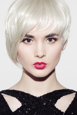 Close-up portret van prachtige model met perfect glanzend blond haar en lichte make-up. Witte achtergrond.
