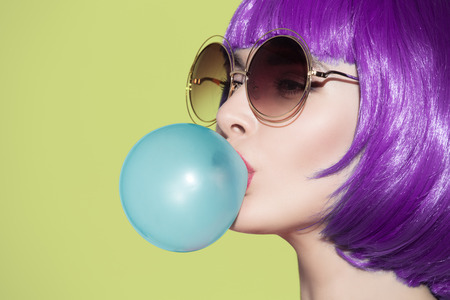 Pop art woman portrait wearing purple wig. Blow a blue bubble chewing gum. Olive background. Standard-Bild