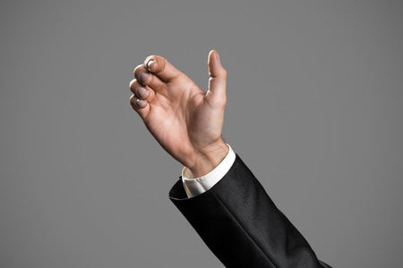 seize: Business Mans Hand To Hold Card, Mobile Phone Or Other Palm Gadget. Isolated On Gray Background. Stock Photo