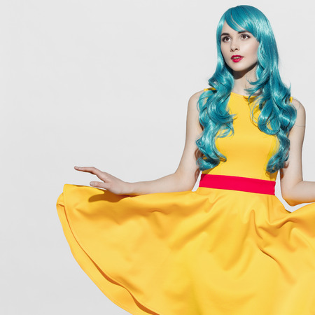 gaga: Pop art woman portrait wearing blue curly wig and bright yellow dress. White background. Space for text.