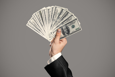 investment concept: Business Mans Hand To Holding Money. Handful Of Dollars On Gray Background. Stock Photo