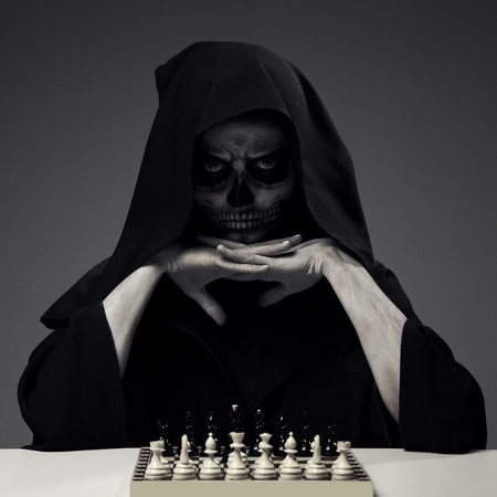 """Concept """"Playing With Death"""". Woman In Realistic Skull Makeup Playing Chess."""