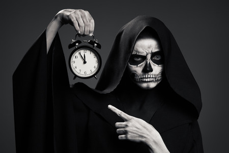 otherworldly: Scary Death Hold A Watch In His Hand. Realistic Skull Makeup. Stock Photo
